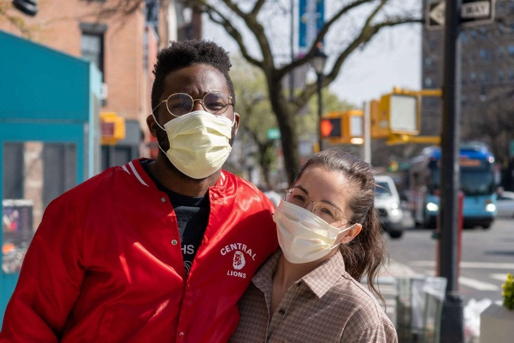 a couple is wearing facemasks